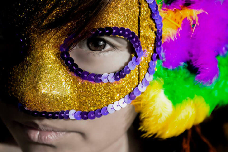 a photo of a girl with a Mardi Gras mask on