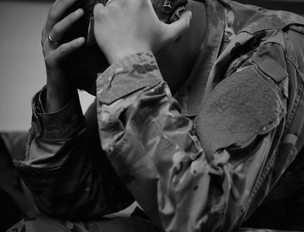 This is a black and white image of a soldier in full uniform holding a gun near his head.